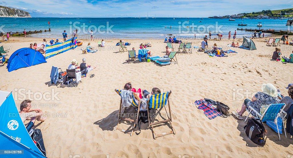 Seaside sunbathers families and tourists on summer beach holidays panorama stock photo
