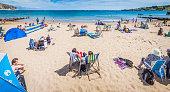Seaside sunbathers families and tourists on summer beach holidays panorama