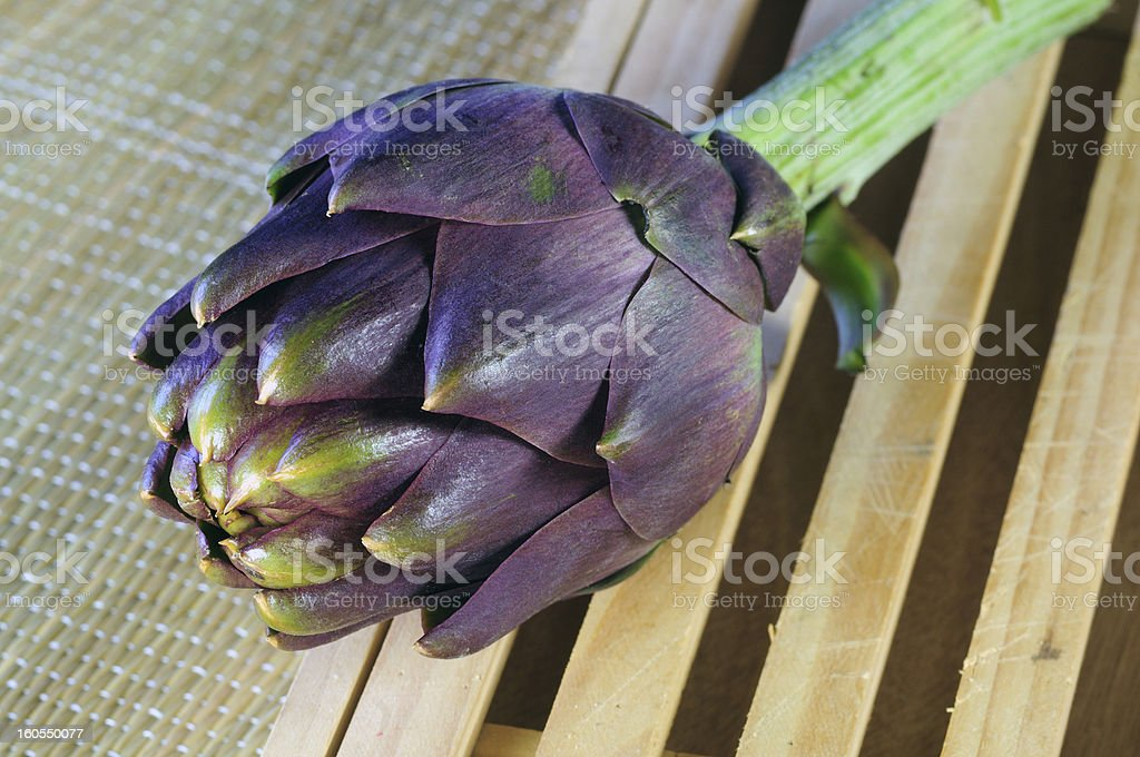 Seasonal artichoke on a chopping board royalty-free stock photo