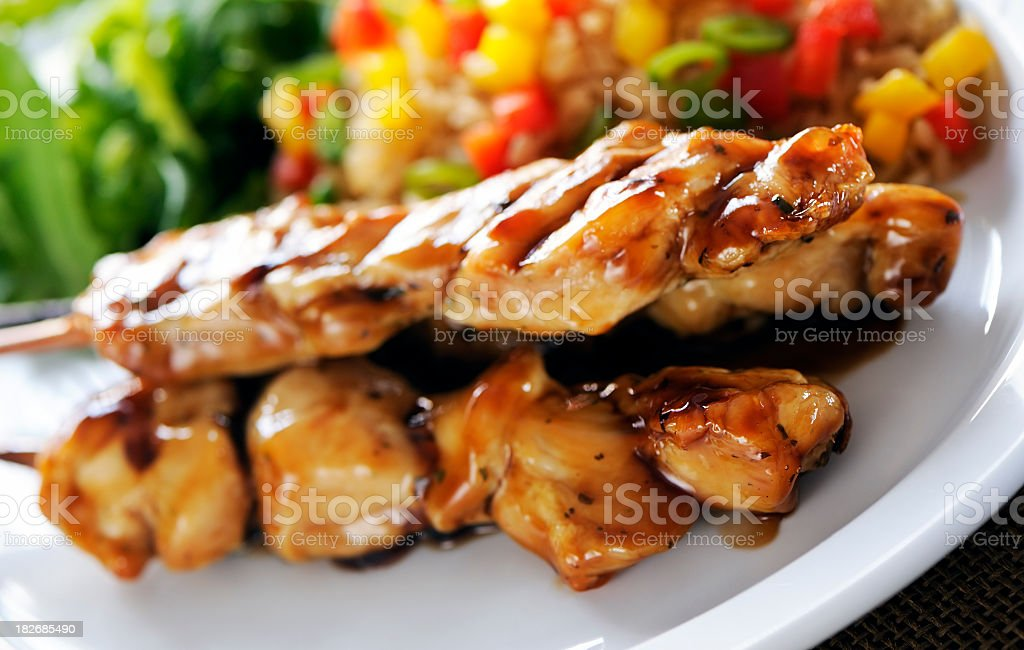 Seasoned chicken on wooden skewers on a white plate royalty-free stock photo