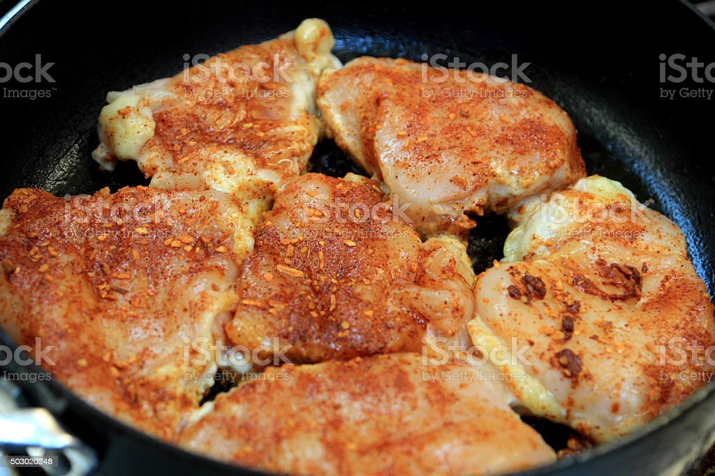 Seasoned chicken thighs being browned in a skillet stock photo