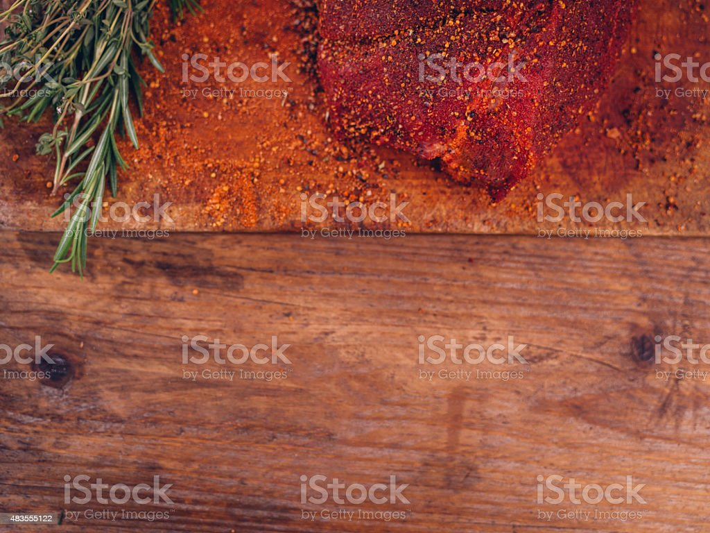 Seasoned piece of pork with herbs on rustic wooden texture stock photo