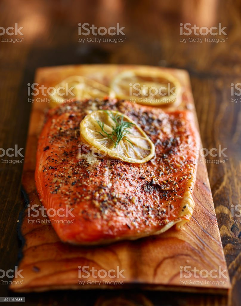 seasoned salmon cooked on cedar plank with dill and lemon stock photo