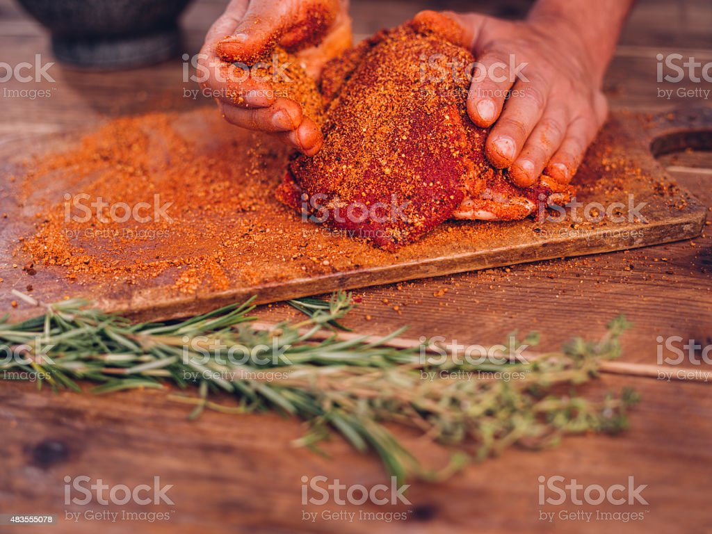 Seasoning of herbs and spices being rubbed into pork stock photo