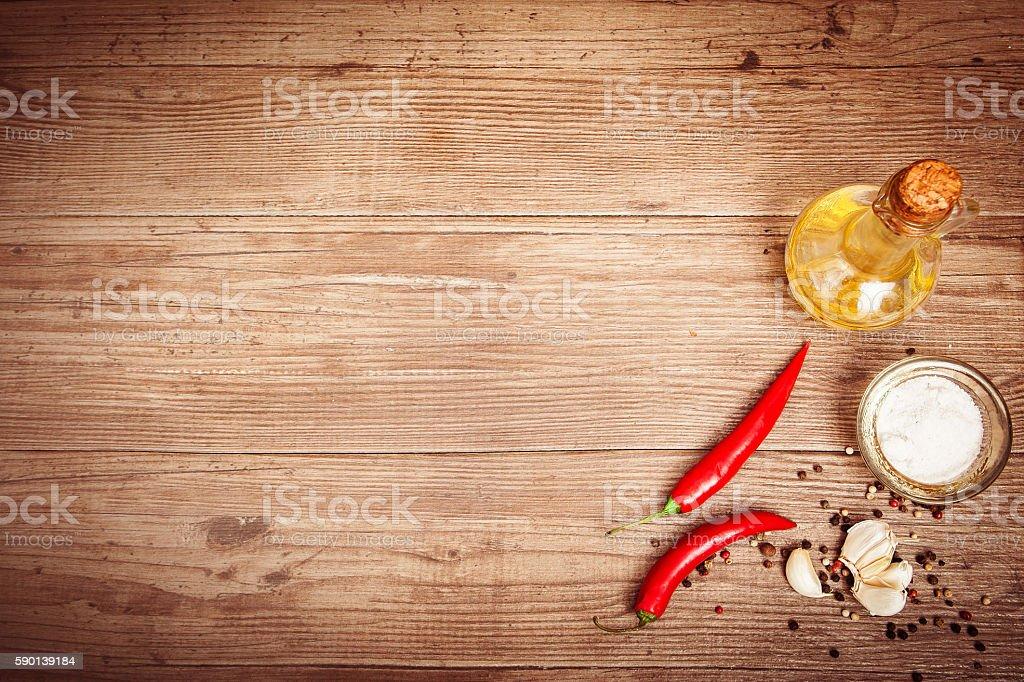Seasoning, olive oil, chili peppers, garlic on dark wooden backg stock photo