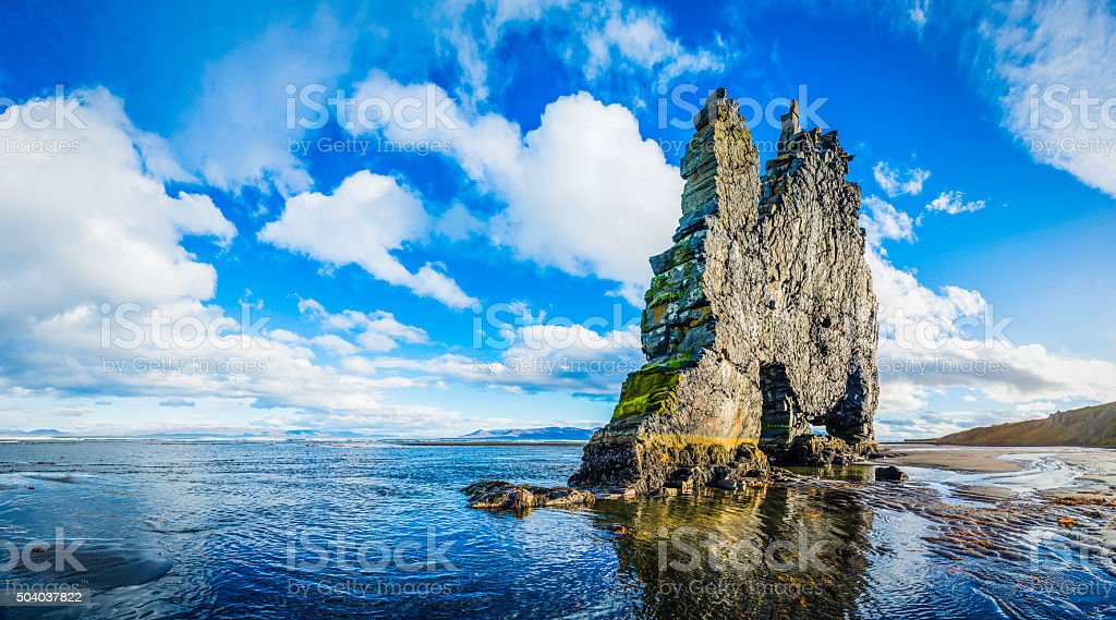 Seastack on ocean beach beneath big sky panorama Hvitserkur Iceland stock photo