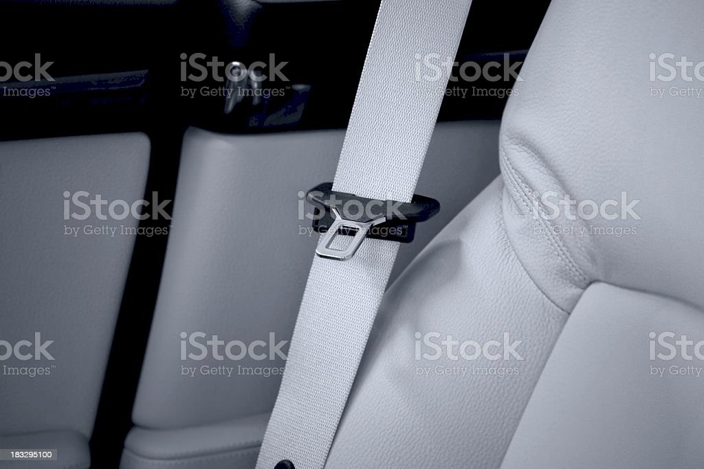 A seat belt in a luxury car with white leather upholstery. royalty-free stock photo