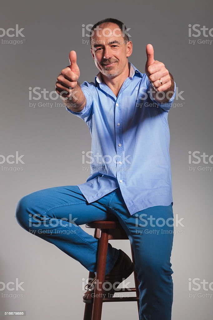 seated bearded man in jeans showing thumbs up stock photo