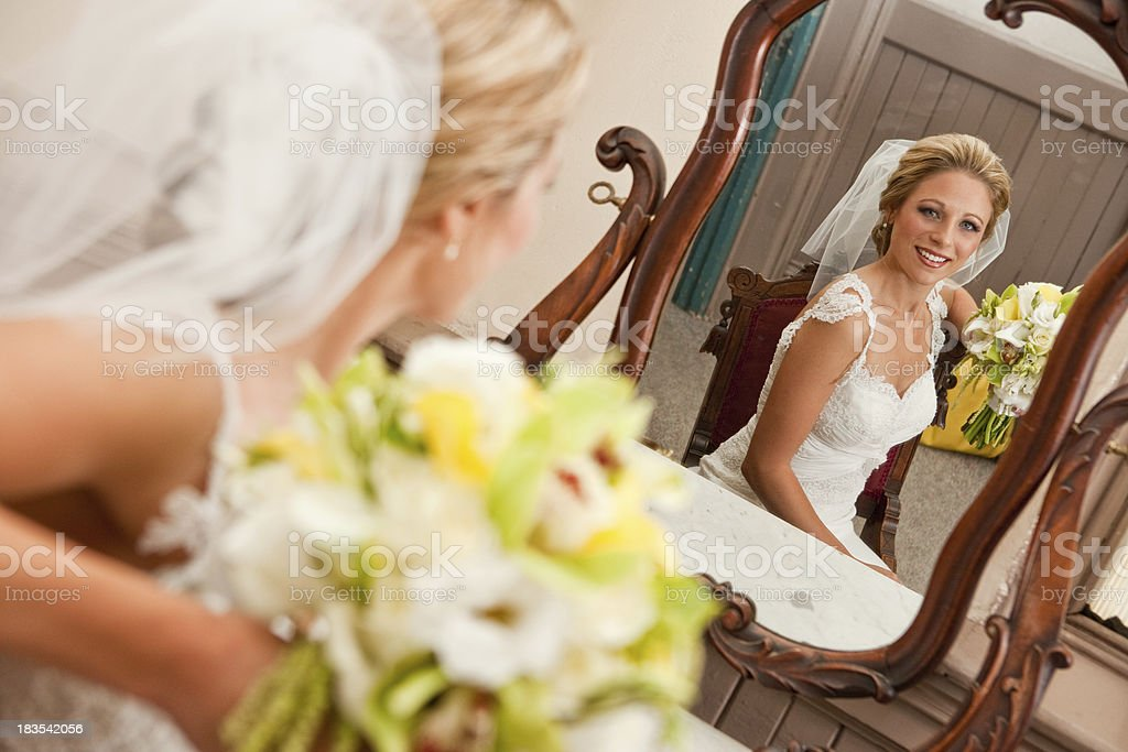 seated bride in wedding dress veil with bouquet antique mirror stock photo