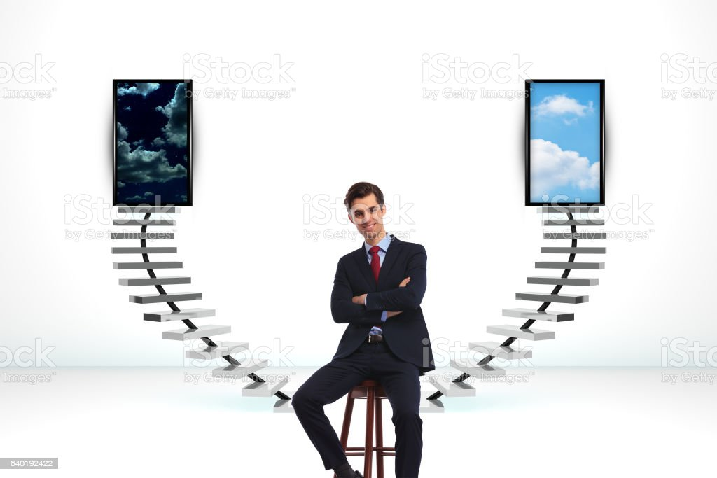 seated happy business man in front of a big decision stock photo