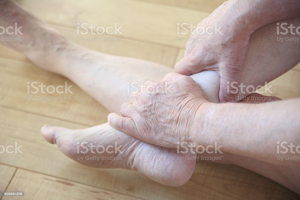 Seated man holding his painful ankle stock photo