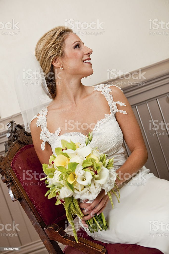 seated smiling bride wedding dress veil with bouquet antique chair stock photo