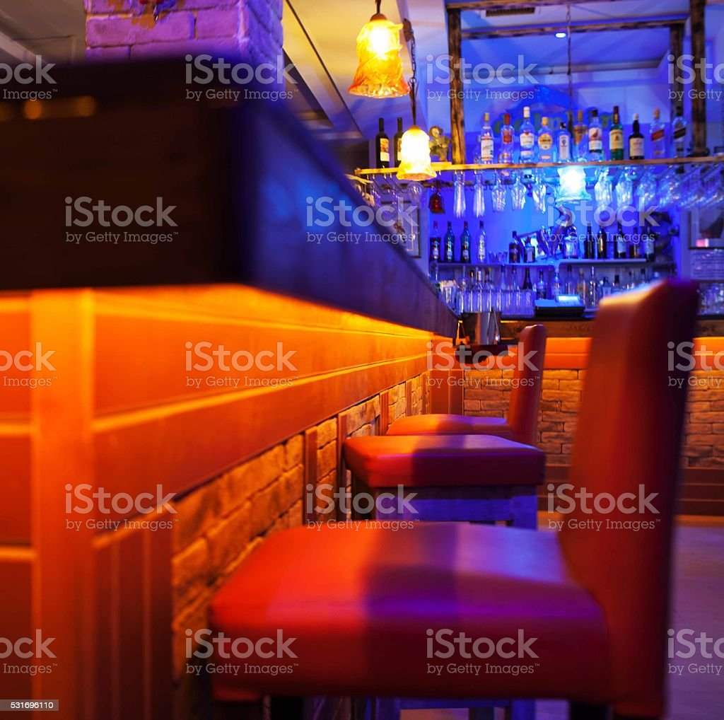 Seats in a brightly lit cocktail bar or nightclub stock photo