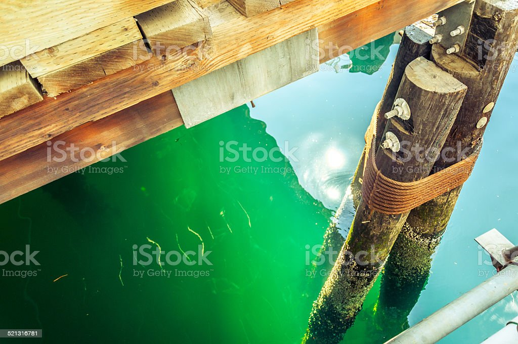 seattle timber-piled wharf and water surface with sun reflection royalty-free stock photo