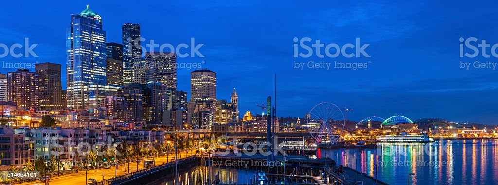 Seattle waterfront harbor downtown skyscrapers and apartments illuminated at dusk stock photo