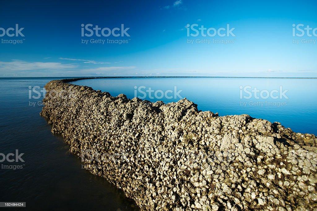 Seawall under deep blue sky stock photo