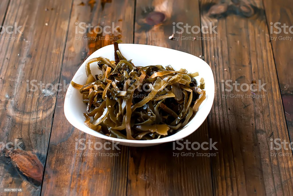 seaweed in a bowl on a wooden table stock photo