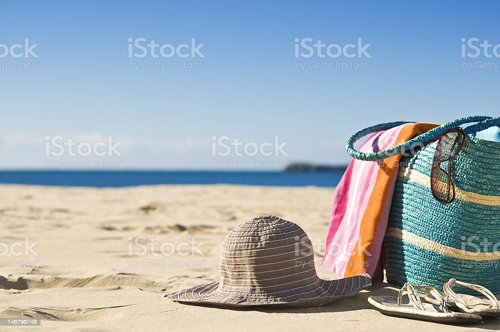 Secluded beach with white sand, a towel and hat stock photo