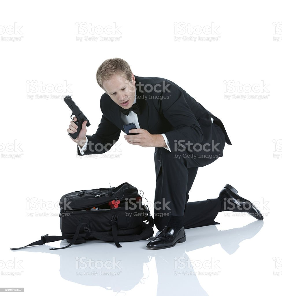 Secret agent holding gun and using Phone royalty-free stock photo