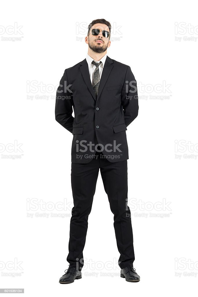 Secret agent or guard with hands behind back wearing sunglasses stock photo