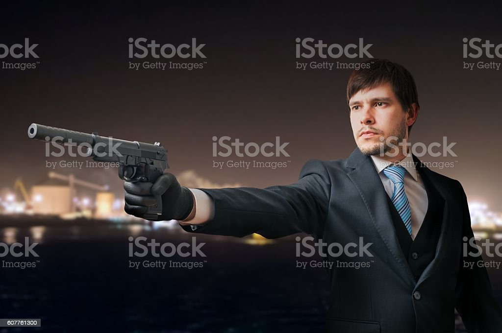 Secret agent or spy is aiming with pistol at night. stock photo