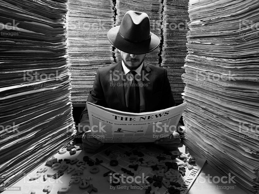 Secret agent reading newspaper in dark for censorship stock photo
