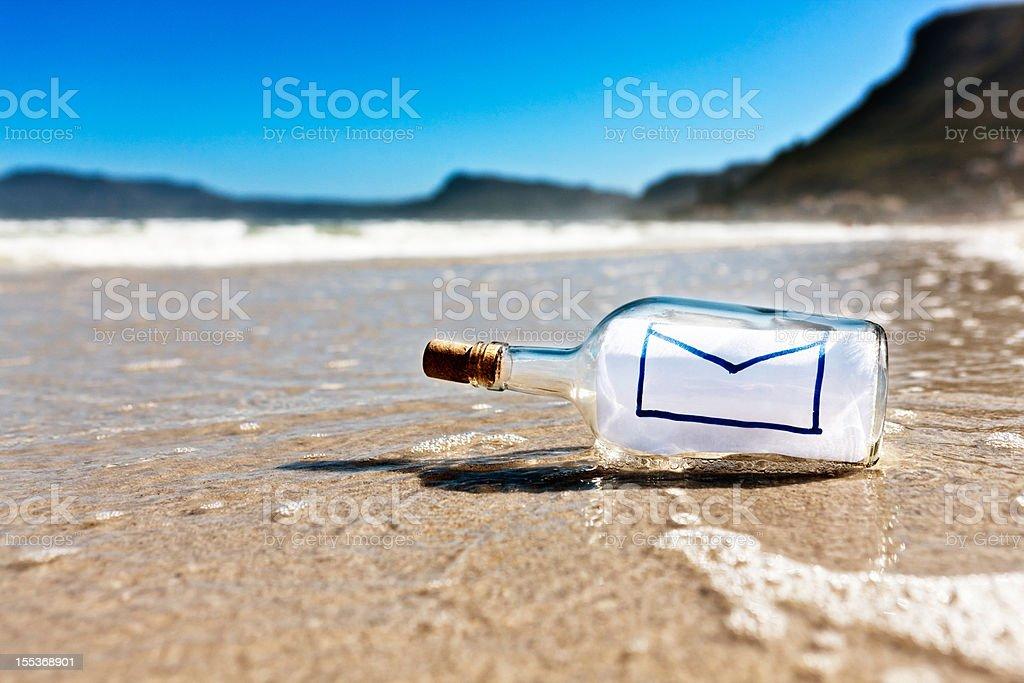 Secret message in a bottle on deserted beach stock photo
