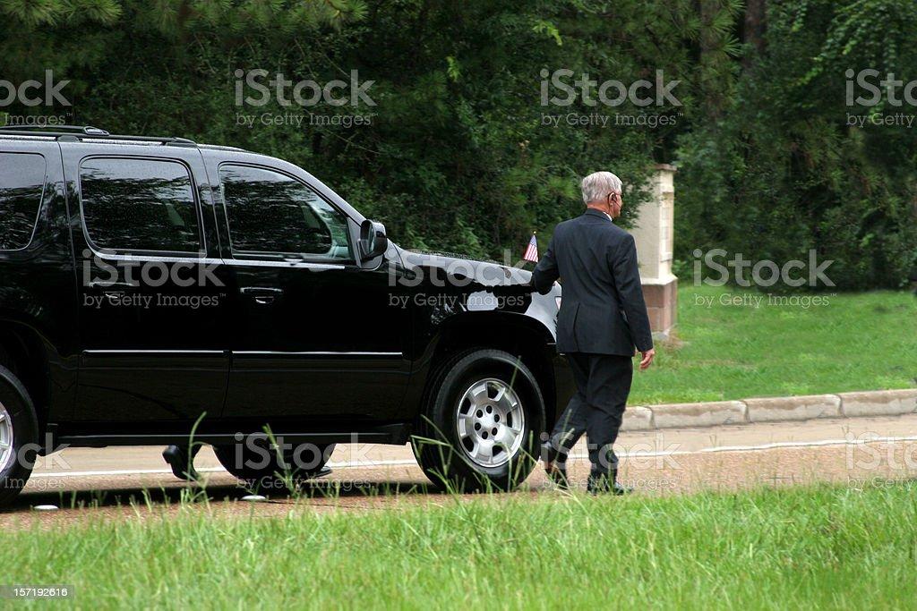Secret Service men walking beside black SUV. Motorcade. stock photo