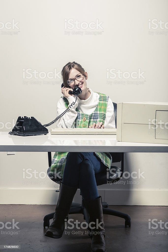Secretary at her Desk Typing while on the Phone royalty-free stock photo
