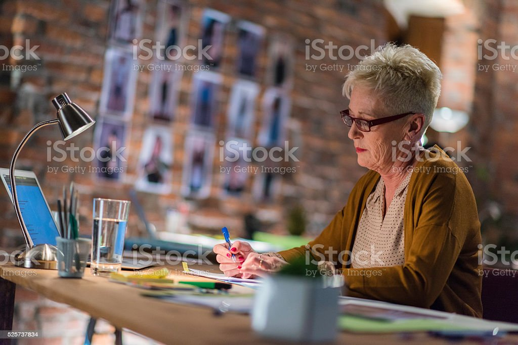 Secretary at work behind a desk in the office stock photo