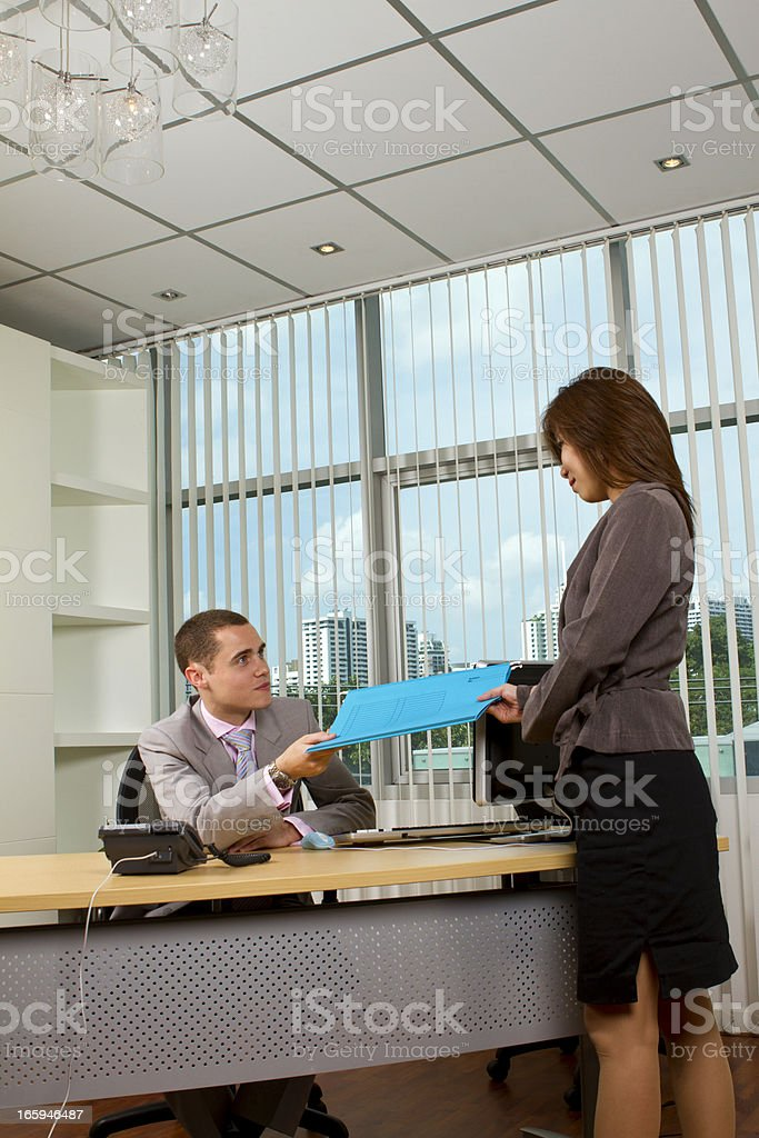 Secretary handing documents over to her manager stock photo