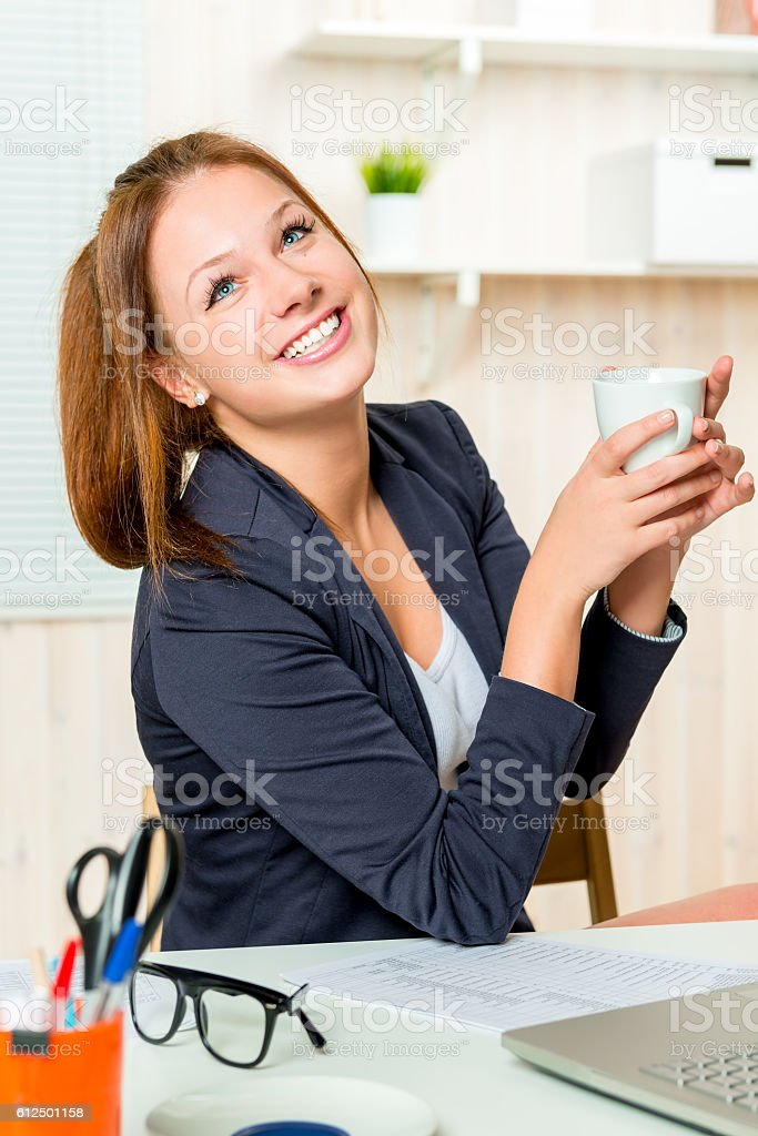 secretary happy with a cup of coffee dreaming about something stock photo