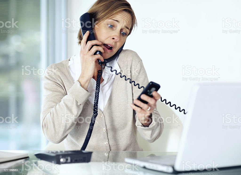 Secretary talking on both a cell phone and telephone royalty-free stock photo
