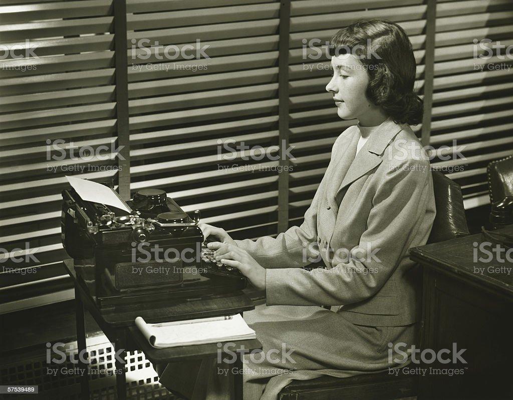 Secretary typing on typewriter in office, (B&W) royalty-free stock photo