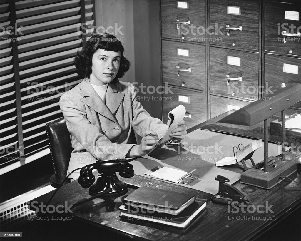 Secretary working in office, (B&W) stock photo
