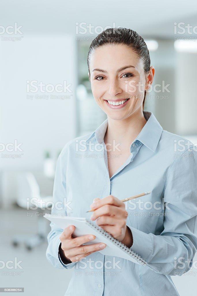 Secretary writing notes on a notebook stock photo