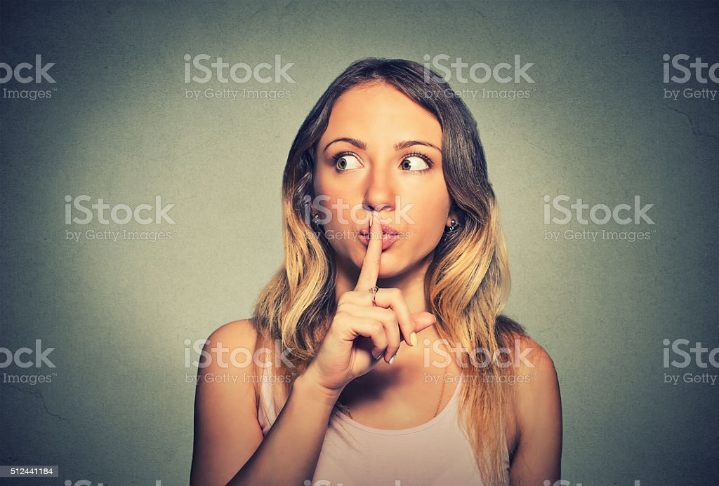 secretive woman placing finger on lips shh, quiet stock photo