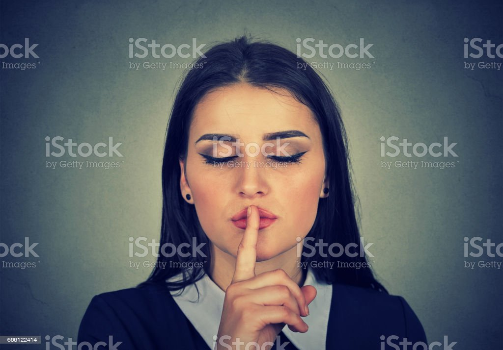 secretive young woman placing finger on lips asking shh stock photo
