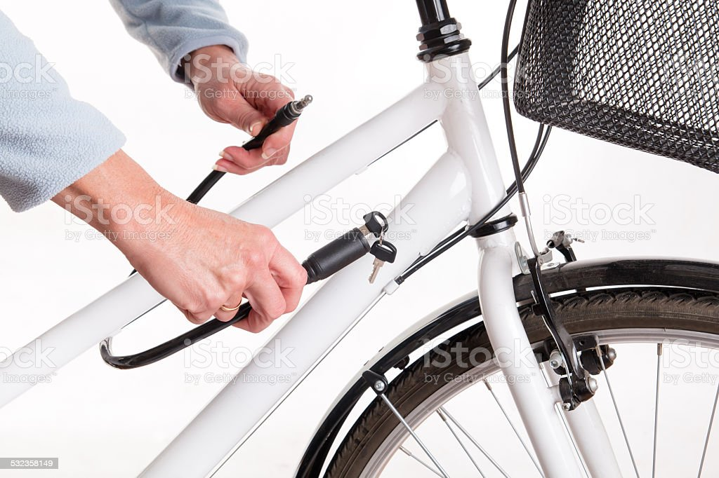 Securing the bike with a chain with a key stock photo