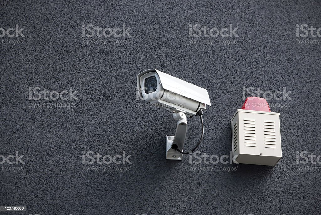 Security camera and alarm box on a black wall stock photo
