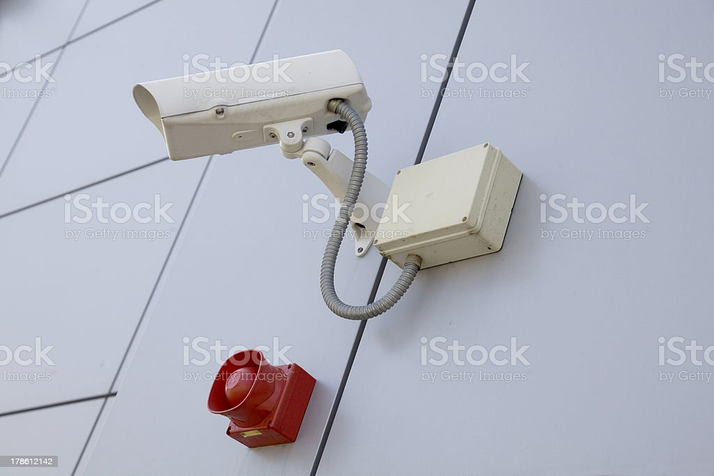 Security Camera and Red Siren Mounted on a Grey Wall royalty-free stock photo