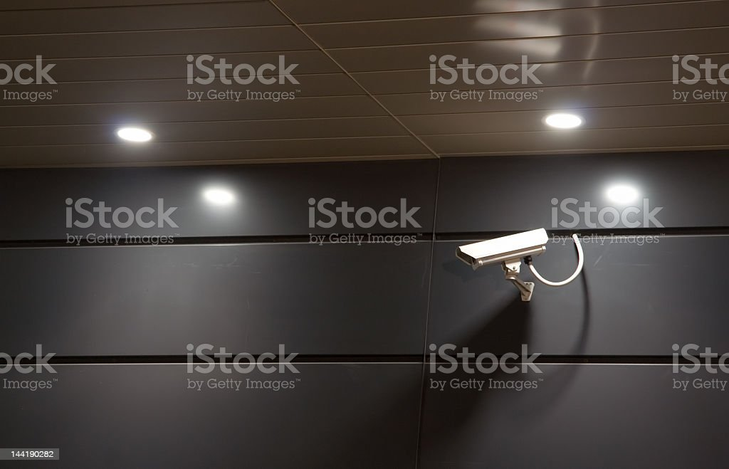 A security camera attached to a dark gray wall stock photo