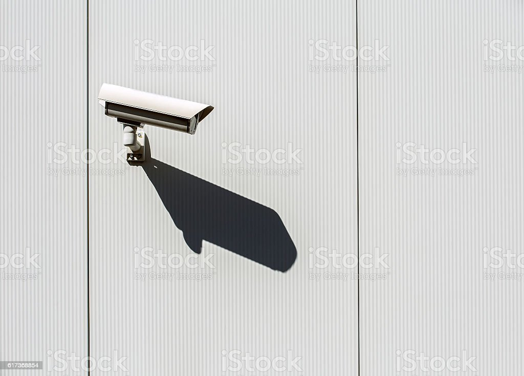 Security camera on a wall. stock photo