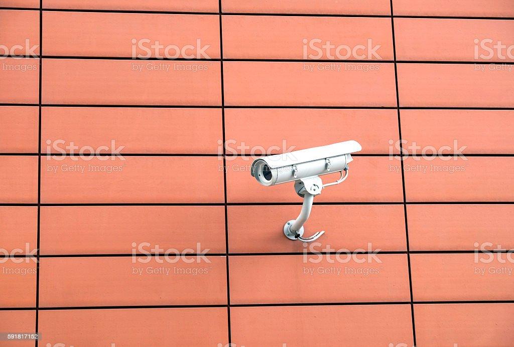 Security camera on orange wall stock photo