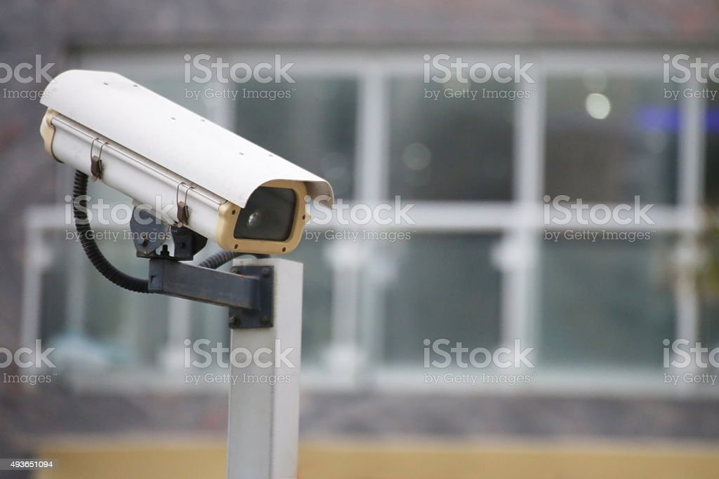 Security camera on top of building watching the entrance stock photo