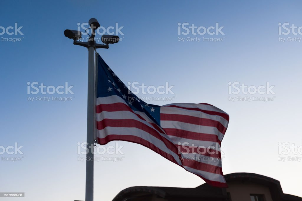 Security cameras and USA flag waving in the sky stock photo