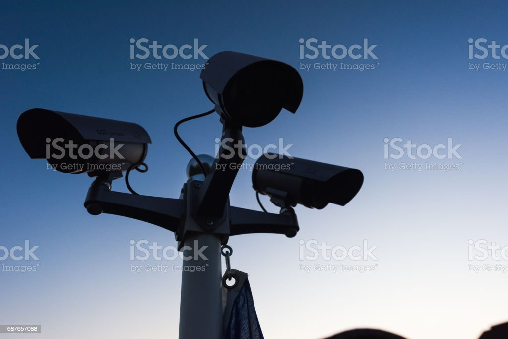 Security cameras in the sky during twilight stock photo