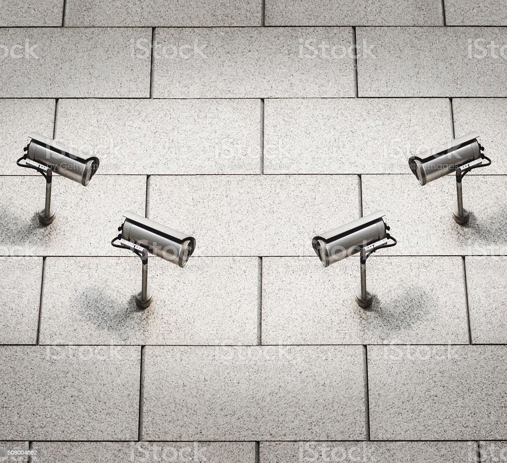 Security cameras on wall watching each other stock photo
