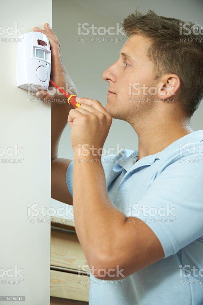 Security Consultant Fitting Burglar Alarm Sensor In Room stock photo