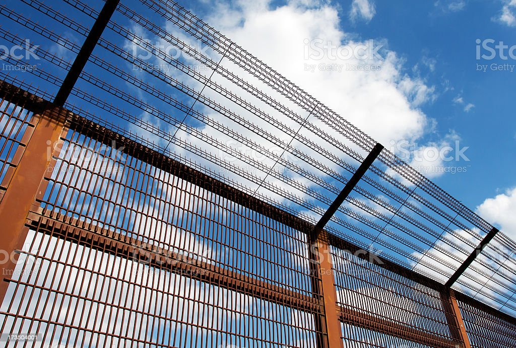 Security fence against blue sky royalty-free stock photo